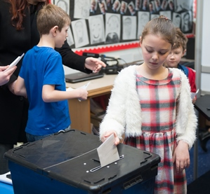Democracy Services at St Wilfrids School, young girl casting a poll vote