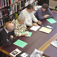 Group around a library desk discussing local history